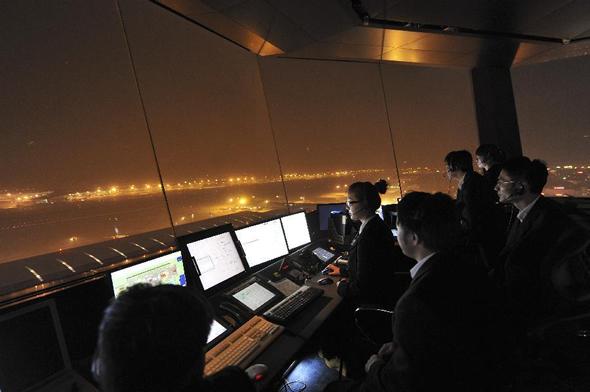 管制员何茜(左)和同事们在首都国际机场塔台指挥航班