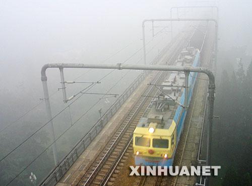 北京 天津/10月26日,浓雾笼罩南京,一列火车在雾中穿行。